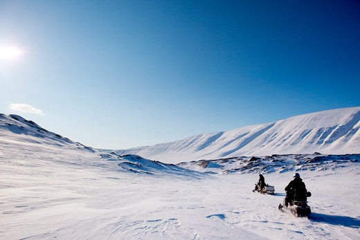 Two snowmobiles on a barren winter landscape, Svalbard Norway : Stock Photo