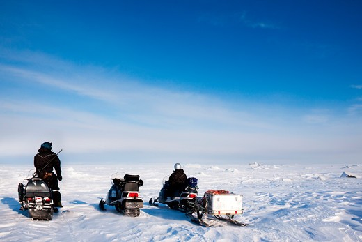 Three snowmobiles on a svalbard landscape of barren snow : Stock Photo