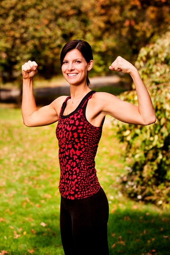 A portrait of a woman flexing her bicep muscles : Stock Photo