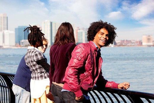 An African American looking at the camera with a group of friends in the background : Stock Photo