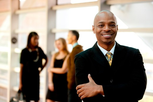 A happy black business man with people in the background : Stock Photo