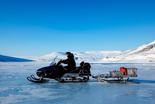 Stock Photo: 4148R-2813 A man on a snowmobile against a winter landscape