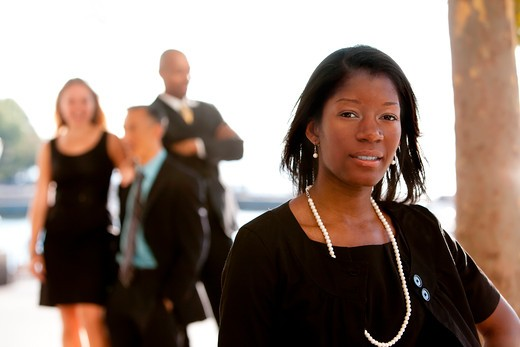 An attractive African American business woman with colleagues in the background : Stock Photo
