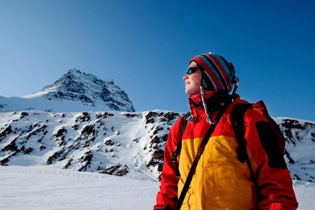 A portrait of a female adventurer against a mountain landscape : Stock Photo