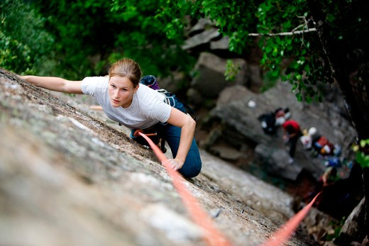 Stock Photo: 4148R-2863 A female climber on a steep rock face.  Shallow depth of field is used to isolated the climber.  Focus is on the head, shoulders and arms of the climber.