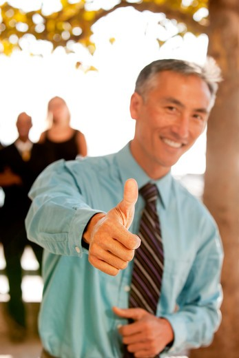 A casual business man with thumbs up : Stock Photo