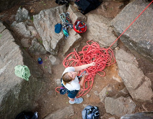 A female climber belaying - viewed from above.  A shallow depth of field is used to isolate the climber - with focus on the eyes and head. : Stock Photo