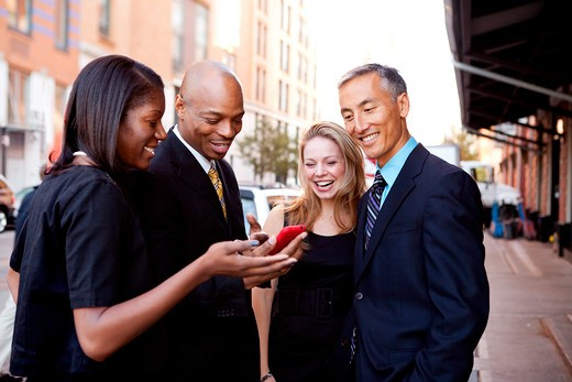 A group of business people looking at a cell phone and laughing : Stock Photo