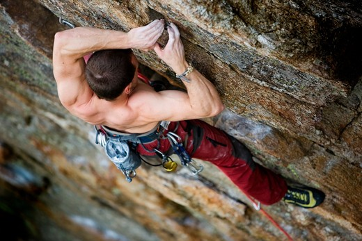 Stock Photo: 4148R-2887 A male climber, viewed from above, climbs a very high and steep crag.