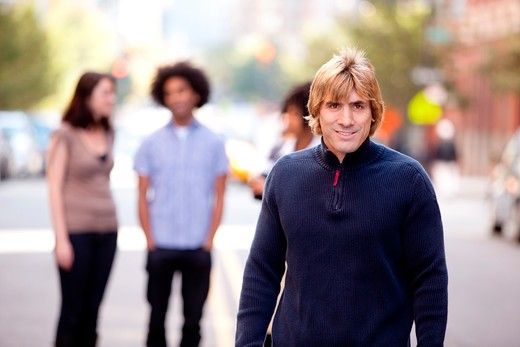 A group of people in a city setting - a caucasian male in the foreground : Stock Photo