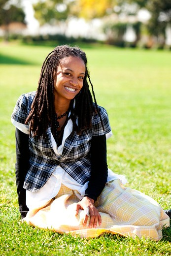 Stock Photo: 4148R-2892 A young African American student sitting on grass