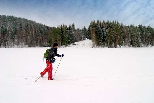 Stock Photo: 4148R-2900 A cross country skier out on a refreshing trip over a frozen lake.