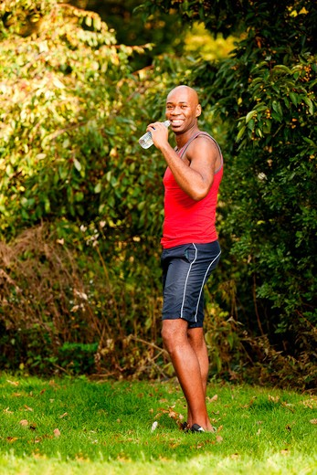 Stock Photo: 4148R-2906 A man exercising in the park, taking a break