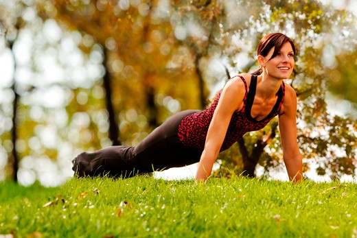 A caucasian female doing push ups in the park : Stock Photo