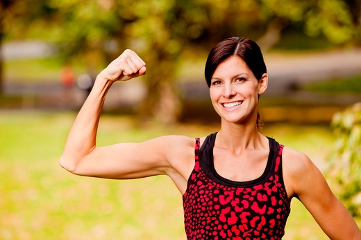Stock Photo: 4148R-2910 A pretty fitness model flexing her bicep