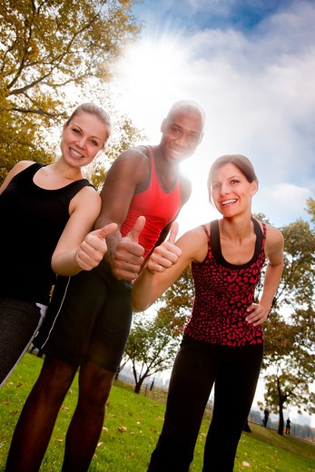 A happy group of people in the park exercising : Stock Photo