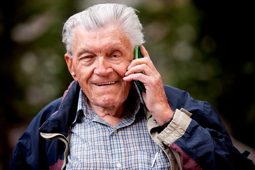 A portrait of a senior using a cell phone outdoors : Stock Photo