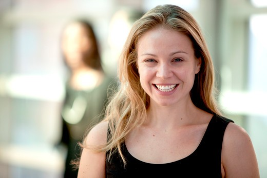 Stock Photo: 4148R-2924 Attractive young blonde woman smiling while looking at camera with woman in background. Horizontally framed shot.