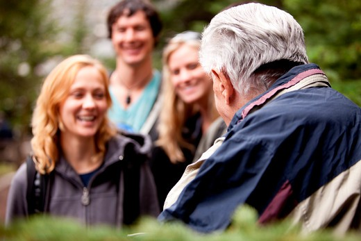 An elderly man talking to a group of young people in the forest. : Stock Photo