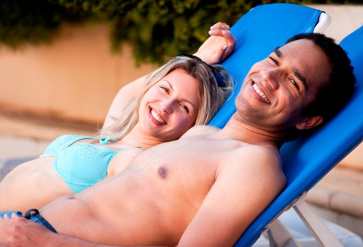 A happy couple looking at the camera relaxing in pool side chairs : Stock Photo