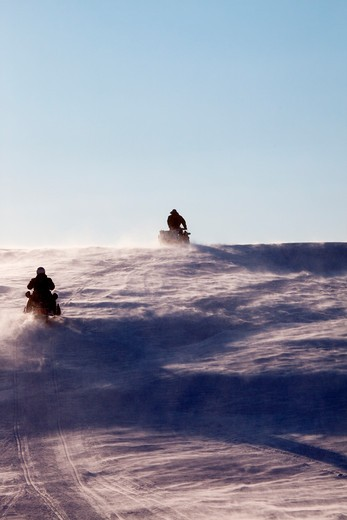 Stock Photo: 4148R-2946 Two snowmobiles driving up a hill in a snow storm
