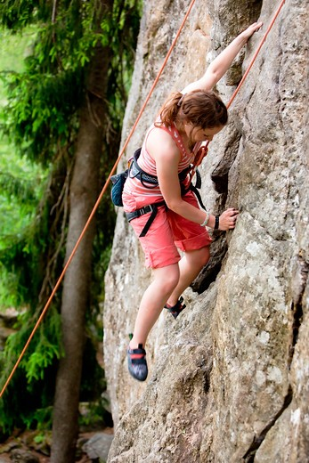 Stock Photo: 4148R-2956 A female climber, climbing using a top rope on a steep rock face (crag).  A shallow depth of field has been used to isolated the climber, with the focus on the head and right hand.