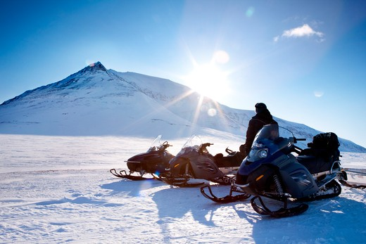 Three snowmobiles and a winter landscape with mountain : Stock Photo