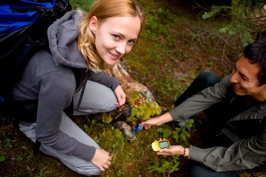 Stock Photo: 4148R-2989 A young man and woman finding a geocache hidden in the forest