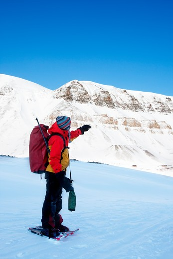 An adventure guide on snowshoes against a winter wilderness landscape : Stock Photo