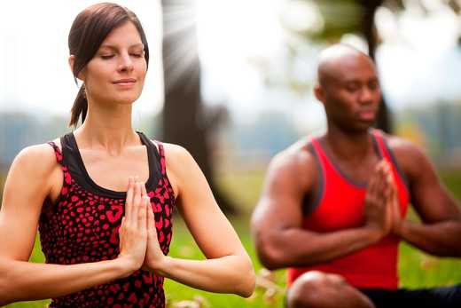 A group of people peacefully meditating in a park : Stock Photo