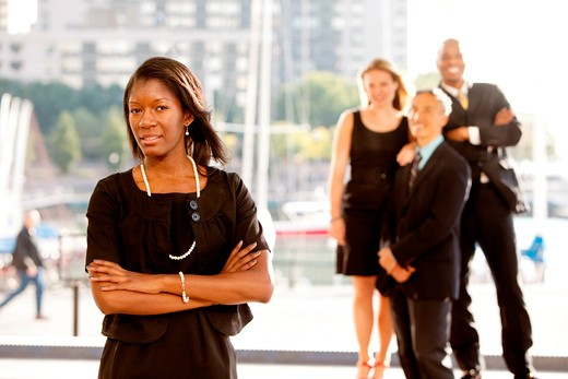Stock Photo: 4148R-3042 Group of four business people with one woman as focus. Horizontally framed shot.