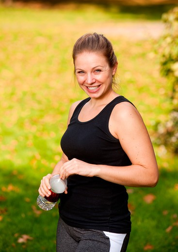 A woman taking a break from exercising in the park : Stock Photo