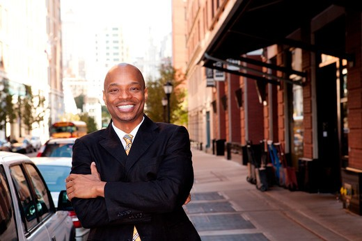 A happy business man on a street in a city : Stock Photo