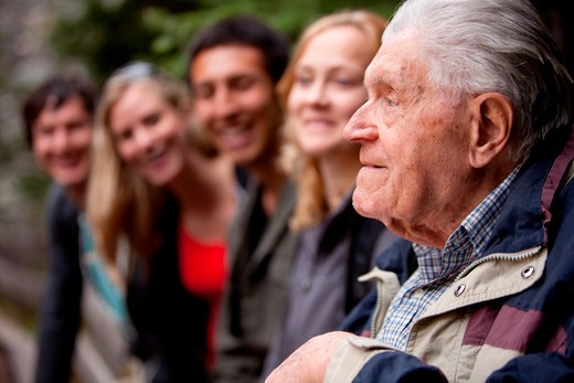 Stock Photo: 4148R-3087 An elderly man telling stories to a group of young people in the forest