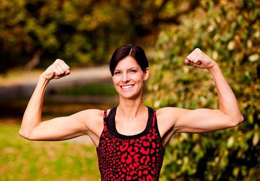 A female fitness model flexing her biceps : Stock Photo