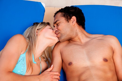 A happy couple kissing while sitting in pool chairs : Stock Photo