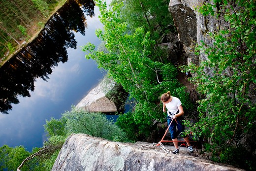 Stock Photo: 4148R-3112 A female climber, repelling down a steep rock face (crag)