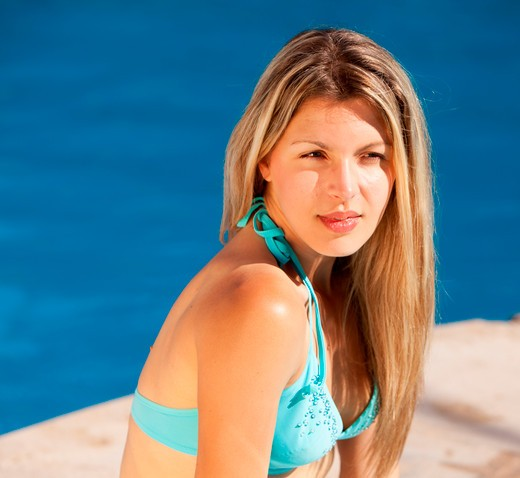 An attractive woman relaxing by an outdoor pool : Stock Photo