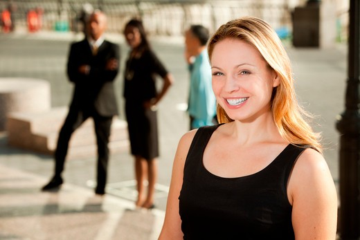 A business woman with colleagues in the background : Stock Photo