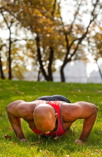 An african american male doing push ups in a park : Stock Photo