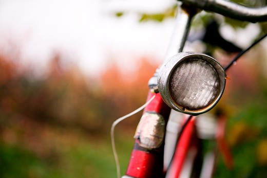 Stock Photo: 4148R-3144 An old red bike detail with a shallow depth of field on a rainy autumn day.