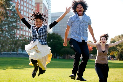 A group of people jumping for joy in a city park : Stock Photo