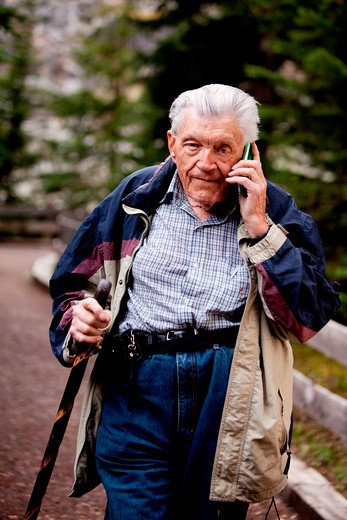 A senior talking on a cell phone outdoors in the forest : Stock Photo