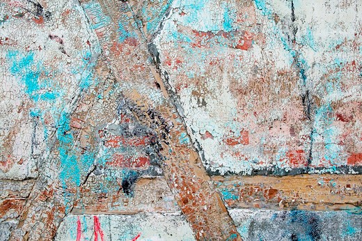 Thick paint and paster slowly peeling off and cracking on an antique wood, brick and plaster building. : Stock Photo