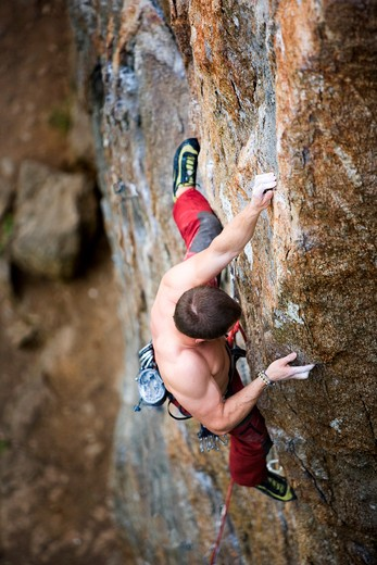 A male climber viewed from above climbs a steep crag. Shallow depth of field is used to isolate the climber with focus on the hands and head : Stock Photo