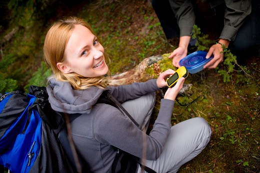 Stock Photo: 4148R-3159 A young woman finding a geocache in the forest