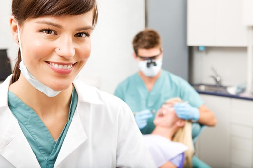 Stock Photo: 4148R-495 A portrait of a dental assistant smiling at the camera with the dentist working in the background