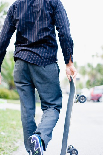 Rear view of a man holding a skateboard : Stock Photo