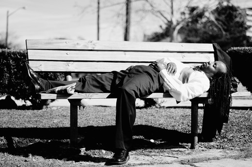 Businessman lying on a bench : Stock Photo