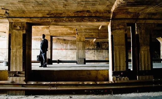Businessman standing in an abandoned building : Stock Photo